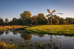 Holländskt polderlandskap nära gouda, Holland med att pumpa väderkvarnen nära en liten sjö i slutet av dagen arkivbild