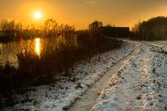 Holländskt vinterlandskap med solnedgång Arkivfoto