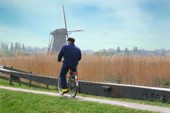 Holland Farmer Riding Bicycle. An unknown farmer wearing yellow clogs while riding his bicycle to windmill on farm in the Kinderdijk area of Holland Stock Photography