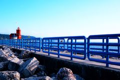 Holland Harbor Light, Big Red. Bright blue fences on the pier, behind the pier is the turquoise water of the Lake Michigan royalty free stock images