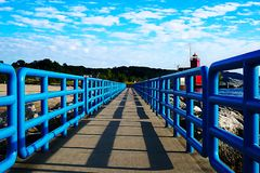 Pier with a bright blue fence in perspective. Big Red Lighthouse on the Lake Michigan. oil paint effect vector illustration