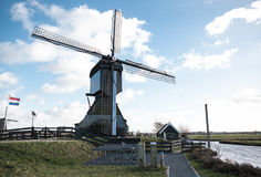 Holland windmill on a canal. Old mill chalk and flour . The beautiful backdrop of the countryside of Holland. Traditional dutch windmill near the canal royalty free stock photography