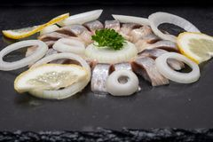 Hollandse Nieuwe- Traditional Dutch Food. Soused raw Herring soaked in mild marinade. Garnished with Lemon, Onion and Parsley. On black natural stone royalty free stock images