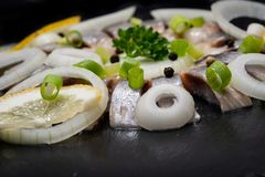 Hollandse Nieuwe- Traditional Dutch Food. Soused raw Herring soaked in mild marinade. Garnished with Lemon, Onion and Parsley. On black natural stone stock image