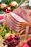 Holliday honey ham. Holiday table setting with delicious whole baked sliced ham, marinated peppers, cherry tomatoes, vegetable salad and glasses of red wine Stock Photo