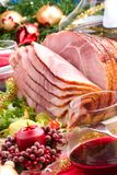 Holliday honey ham. Holiday table setting with delicious whole baked sliced ham, marinated peppers, cherry tomatoes, vegetable salad and glasses of red wine Royalty Free Stock Images