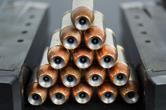 Hollow point, copper jacketed bullets stacked in a pyramid betwe Royalty Free Stock Images