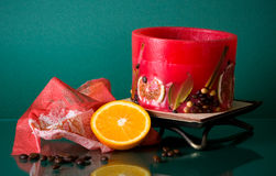 Hollow red round fruit candle with half of orange Stock Image