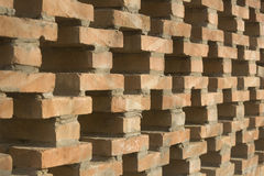 A  hollowed out brick wall. View in depth of a brick wall with nets of crossing shaped holes as background Stock Photography