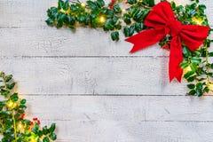 Holly Christmas Background con le bacche e l'arco fotografie stock