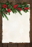 Holly and Fir Border. Christmas abstract background border with holly, ivy, cedar cypress and fir on parchment paper over old oak wood royalty free stock photos