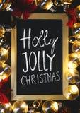 Holly Jolly Christmas Typography sur le tableau noir entre Bul léger images stock