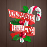 Holly Jolly. Holiday greeting card with calligraphy and decorative elements. Handwritten modern lettering with candy cane, holly and gingerbread man on dark Stock Photography