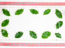 Holly leaves and red ribbon Royalty Free Stock Image