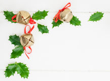Holly leaves  and sleigh bells Royalty Free Stock Images