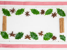 Holly leaves spices and red ribbon Stock Image