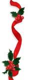 Holly ribbon decoration. Hanging red ribbon, shiny holly and bright berries Stock Photos
