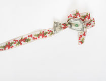 Holly Ribbon Tied Dollar Bill. Holly ribbon tied around US dollar bill with trailing ribbon. Concept of squeezing the dollar to go further during the holidays or Royalty Free Stock Image