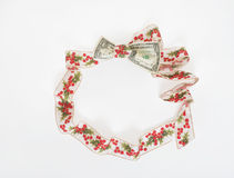 Holly Ribbon Wreath with Dollar Bill. Holly ribbon tied around US dollar bill forming a wreath. Concept of squeezing the dollar to go further during the holidays Stock Photography