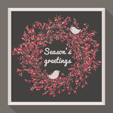Holly wreath with two pretty birds. Seasons greetings Royalty Free Stock Images