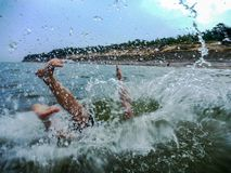 Young men jumps in water. Hollyday on baltic sea Latvia beach uns water spashes Stock Photo