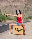 Hollywood Bound. Beautiful young woman with luggage case hitch hiking on lonely desert road to Hollywood, CA stock images
