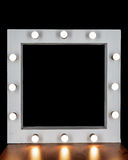 Hollywood lights. makeup spot. White frame with light bulbs and black square inside Stock Photos