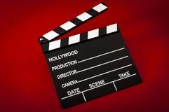 Hollywood och begreppet för filmbransch med ett bräde för tappningfilmclapper på röd bakgrund arkivfoton