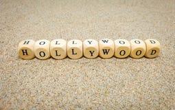 hollywood ord som byggs med träkuber och svarta bokstäver på golvet och botten av sandstranden arkivfoton