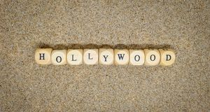 hollywood ord som byggs med träkuber och svarta bokstäver på golvet och botten av sandstranden royaltyfria foton