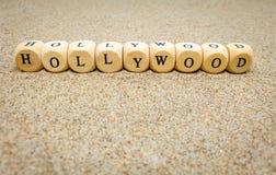 hollywood ord som byggs med träkuber och svarta bokstäver på golvet och botten av sandstranden royaltyfri fotografi