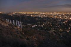 Hollywood-Schriftzug und im Stadtzentrum gelegene Los Angeles-Nachtansicht lizenzfreie stockbilder