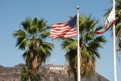 Hollywood sign and american flag. Hollywood sign at the top of a mountain and a USA flag in the foreground, in Los Angeles, California Stock Image