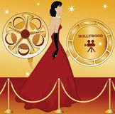 Hollywood Starlet. Walking the red carpet with film reels behind Stock Photography