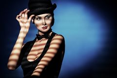 Hollywood style. Elegant young woman posing in vest and black pot hat. Light and shadow royalty free stock photos