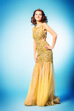 Hollywood style. Fashion shot of a stunning woman in luxurious golden dress. Full length portrait stock image