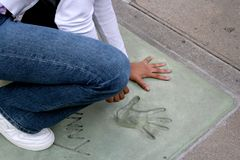 Hollywood Tourist. Children tourist in Hollywood, California. Comparing hand print of the stars at popular attraction Stock Photos