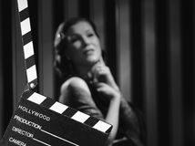 Hollywood woman and clapboard. Hollywood black and white, a beautiful acting woman and a clapboard - minimal lighting and strong contrast stock photo