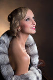 Hollywood woman with fur. Classy lady with fur posing in hollywood 1920s style royalty free stock images