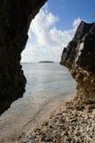 Holmen i bakgrund between vaggar på havskust arkivfoton