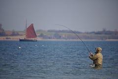 Holnis, Alemania - 8 de abril de 2018 - pescador que se coloca cintura-profundo en el agua de la playa con el velero clásico en e Fotos de archivo