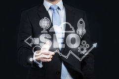 A hologram of business icons and a businessman offering handshake. Stock Photo