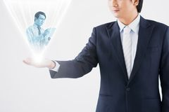 Hologram projection. Cropped image of businessman holding hologram projection of his colleague: technology and communication concept Stock Images