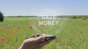 Hologram of Save money on a smartphone. Person activates holographic image on the phone screen on the field with blooming poppies stock video