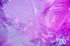 Holographic background in the style of the 80-90s. Real texture of cellophane film in bright acid colors. stock photos