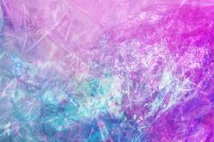 Holographic background in the style of the 80-90s. Real texture of cellophane film in bright acid colors. royalty free stock images