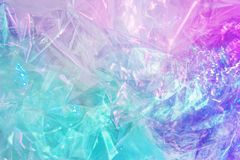 Holographic background in the style of the 80-90s. Real texture of cellophane film in bright acid colors. royalty free stock photo