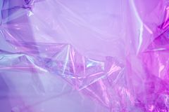 Holographic background in the style of the 80-90s. Real texture of cellophane film in bright acid colors. royalty free stock photography