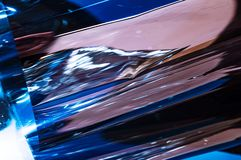 Holographic plastic wrinkled film with contrast sun light reflections. Blue tones with dark black shadows. On metallic chrome surface. Neon light colors royalty free stock photo