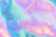 Holographic real texture in blue pink green colors with scratches and irregularities stock image
